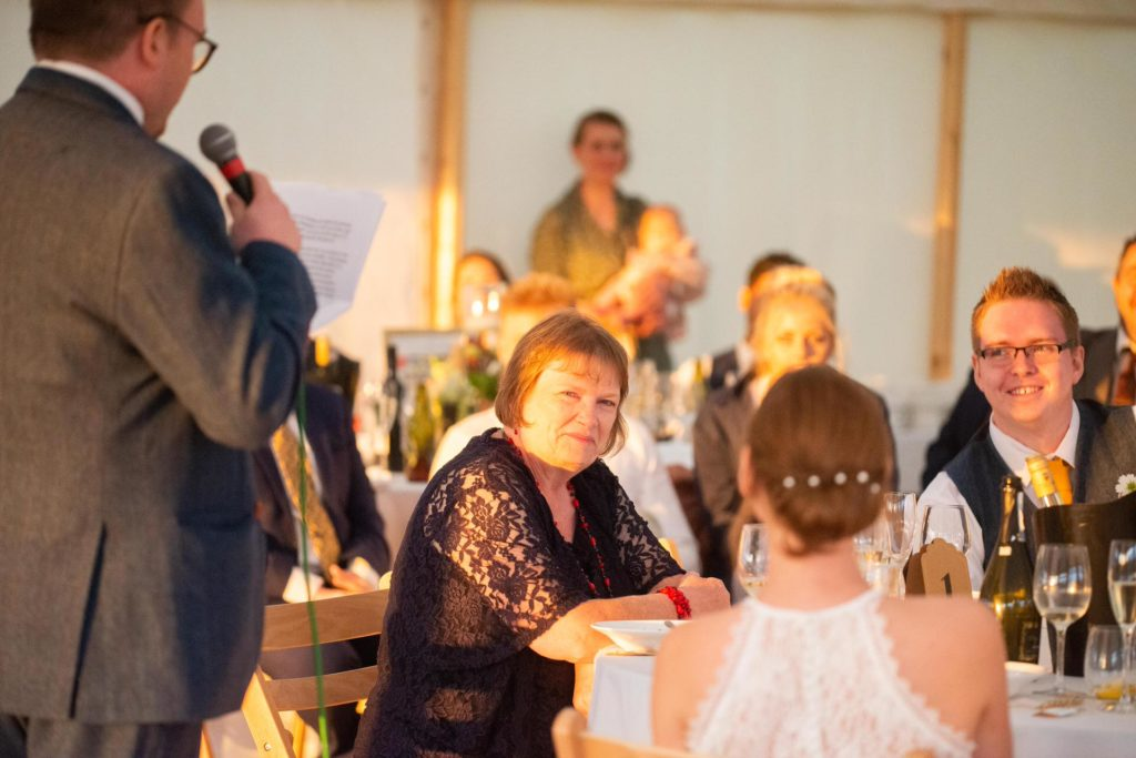 mother of the groom listens to son's speech