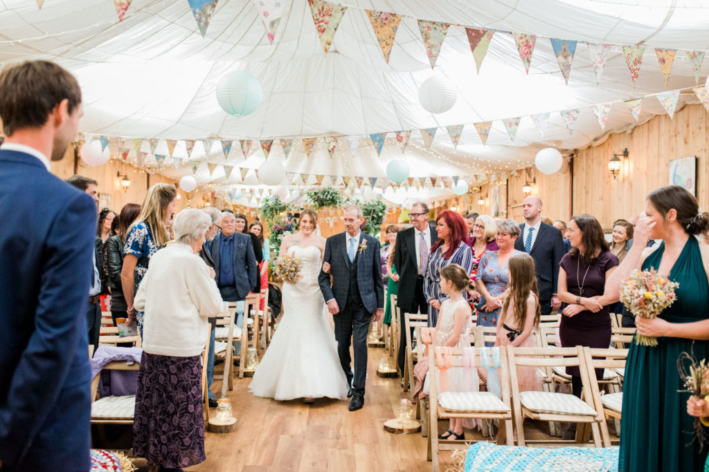 bride and her dad walk down the aisle at wellbeing farm