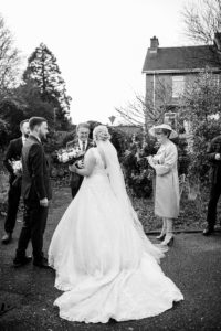 black and white photo of bride outside church