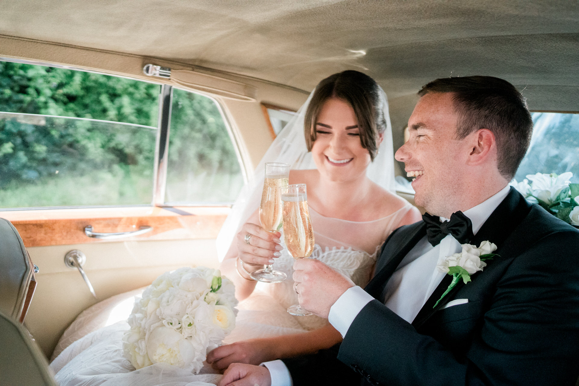 bride and groom in wedding car with champagne toast