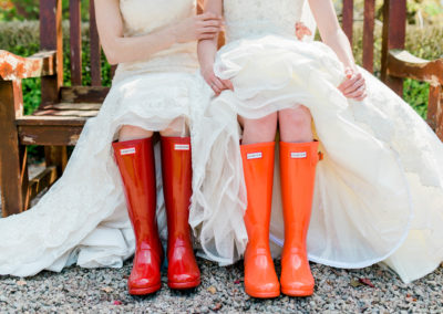 two brides wearing red wellies