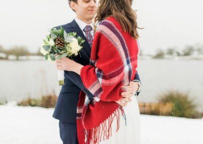 bride and groom cuddle in the snow with red checked blanket