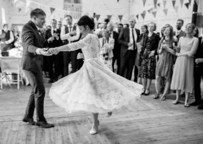 black and white photo of first dance with swirling tea length dress
