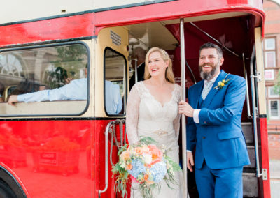 bride and groom on a big red bus