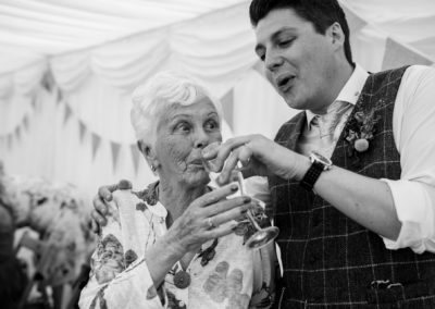 giving granny a sip of champagne
