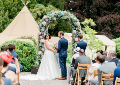 outdoor tipi wedding in Wales with flower arch