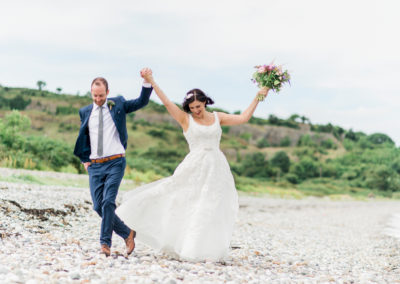 bride and groom dance on beach at anglesey
