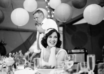 classic bride with dark wavy hair laughing at speech