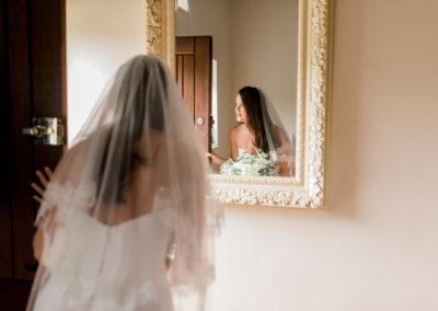 bride peeps through door in front of a mirror