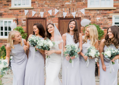 bride and bridesmaids wearing silver and laughing