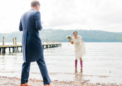 bride with pink wellies paddling in lake windermere
