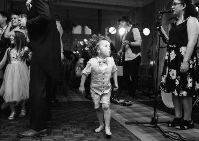 little boy with curly hair jumping on dancefloor