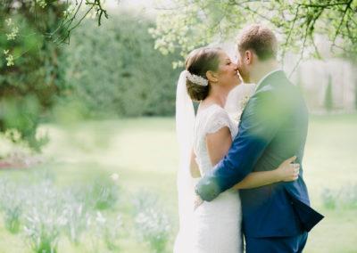 bride and groom kissing in woods