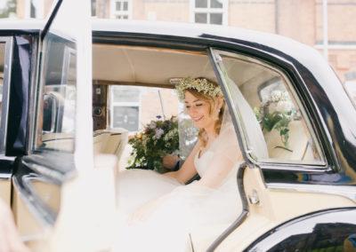 bride with flower crown in wedding car